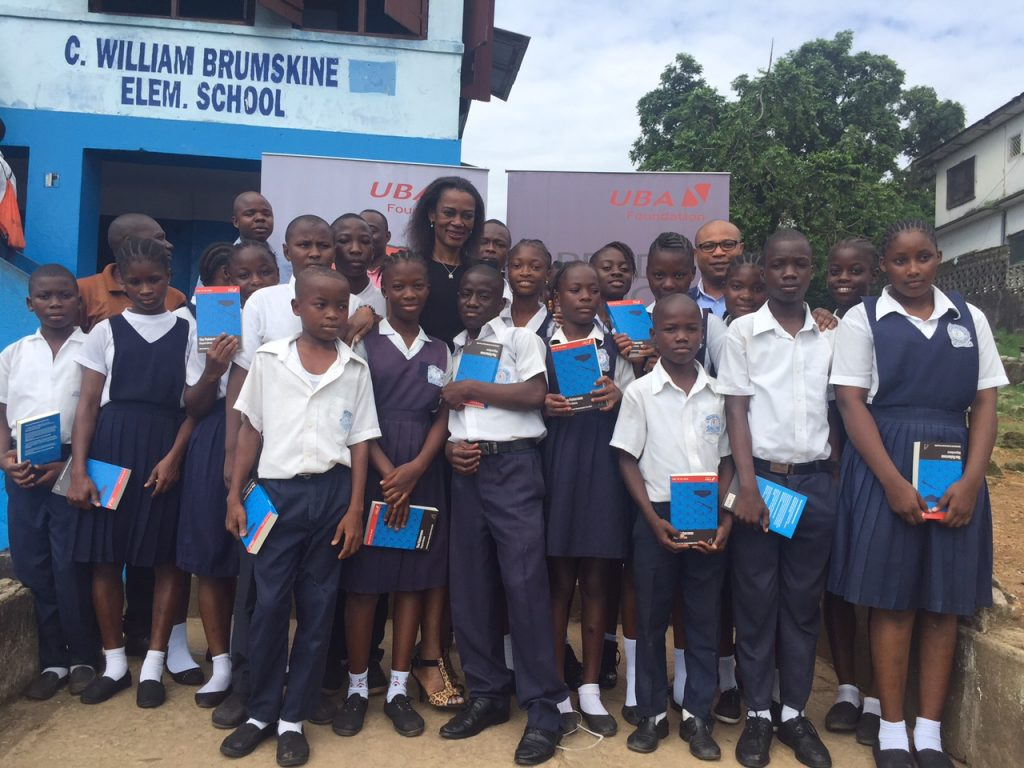 Group Head, Marketing and Corporate Communications, United Bank for Africa( UBA) Bola Atta flanked by pupils of C. William Brumskine elementary school, Monrovia, during a visit to the school as part of UBA foundations Read Africa, Initiative